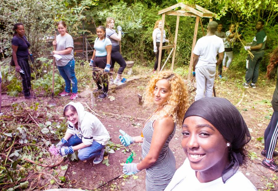 Group of young people outside planting and smiling at the camera